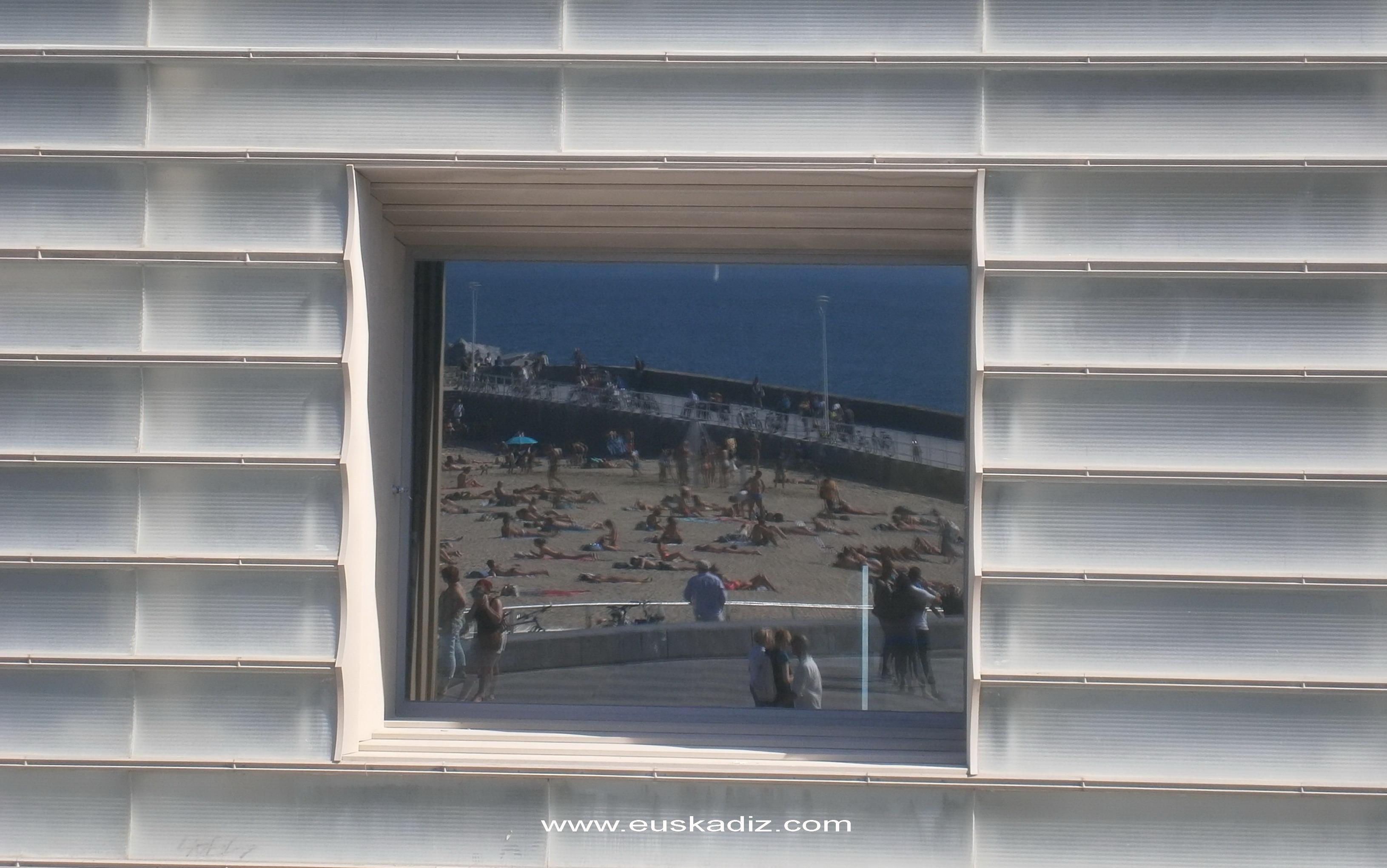 La playa de la Zurriola reflejada en los Cubos del Kursaal.